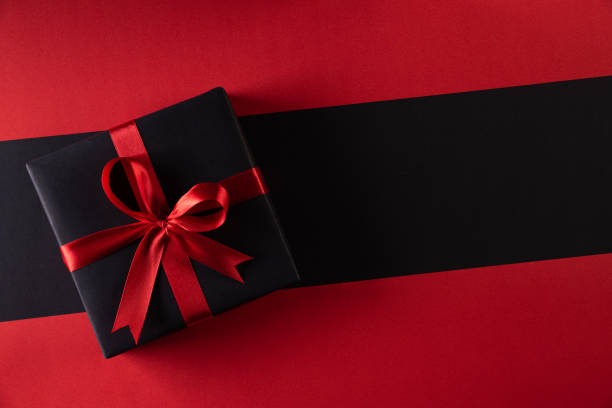 top view of black christmas boxes with red ribbon on black background with copy space for text. black friday and boxing day composition. - regalo natale foto e immagini stock