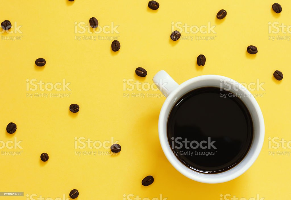 Top view of black coffee and beans on yellow background stock photo