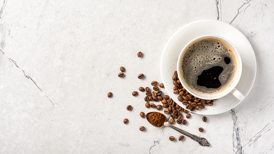 Top view of black coffee in white cup for breakfast on marble background with copy space
