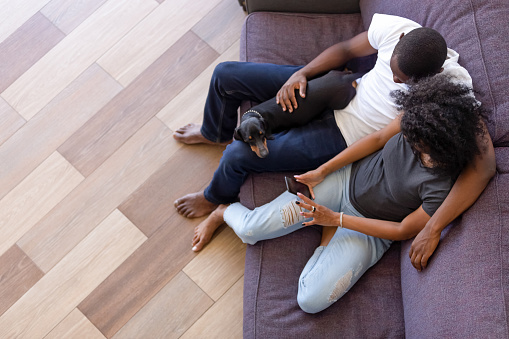 Top view of black couple with dog relax using smartphone