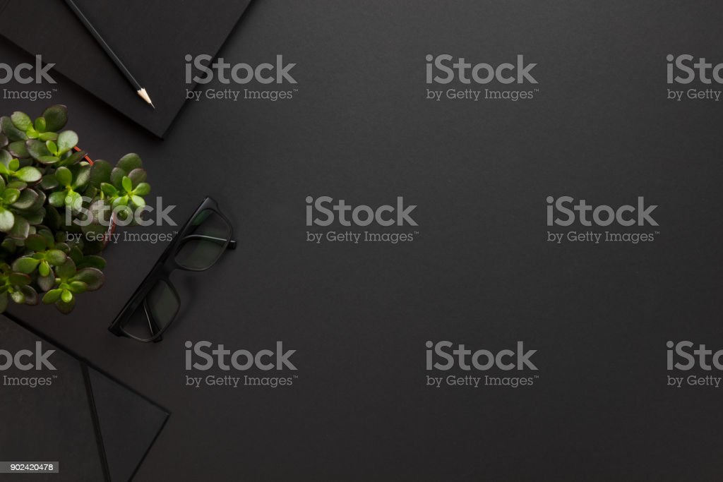 Top view of black office desk with notebook and supplies stock photo