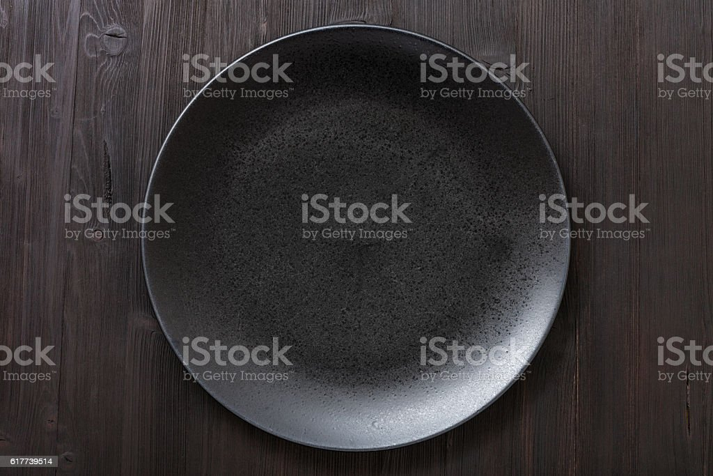 top view of black plate on dark brown table stock photo