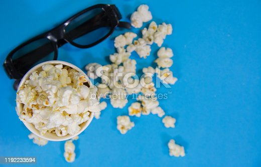 956942702 istock photo top view of black popcorn box full of popcorn with spread popcorn and 3d black cinema glasses on vibrant blue background Film Movie background 1192233594