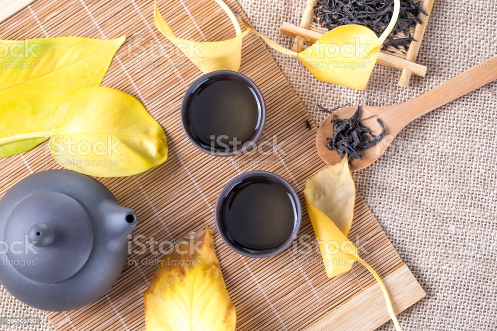 Top view of black teapot and cups with yellow leaves on the table. Hot drinks. Autumn tea. royalty-free stock photo