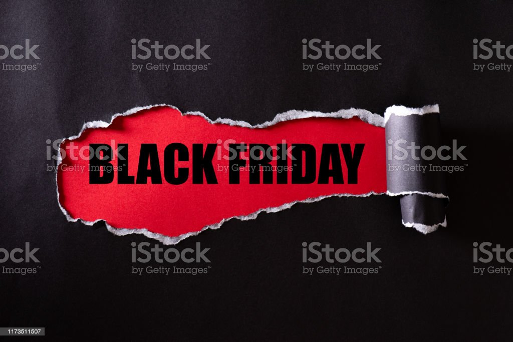 Top view of Black torn paper and the text black friday on a red background. Black Friday composition. Top view of Black torn paper and the text black friday on a red background. Black Friday composition. Advertisement Stock Photo