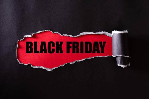 top view of black torn paper and the text black friday on a red background. black friday composition. - black friday imagens e fotografias de stock