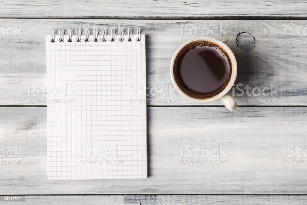 Top view of blank note pad and coffee cup on white wooden table stock photo