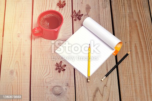 Blank notebook and coffee red cup on wooden