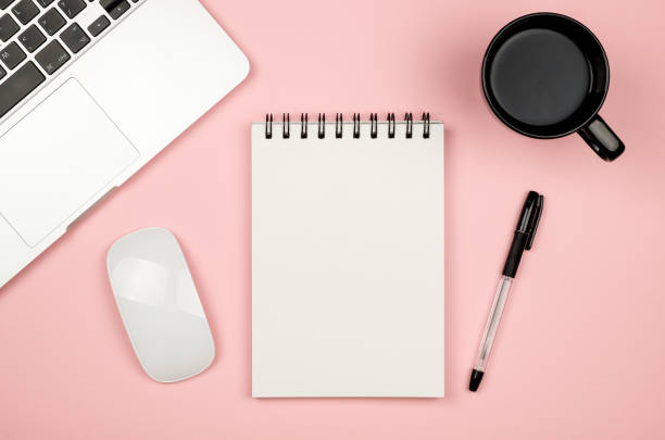 Top view of blank notebook page on pastel colored background office desk with different objects. Minimal flat lay style stock photo