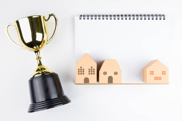 Draufsicht der leeren Notebook Whitepaper, Papier-Haus-Modell und Goldene Trophäe isoliert auf weißem Hintergrund mit Platz für Ihre Nachricht. Konzept-Gewinner – Foto