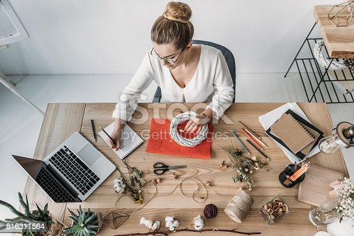 istock top view of blonde female florist working with laptop and dry flowers at workplace 816311564