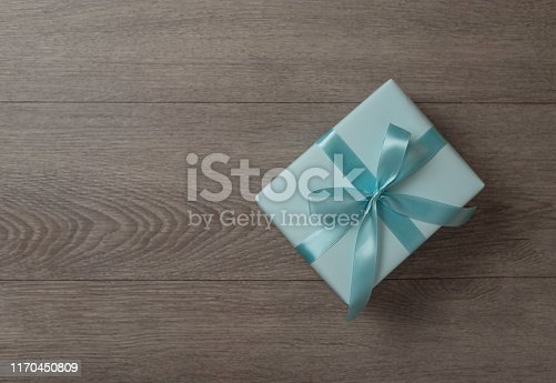 istock Top view of Blue gift box on wooden background. 1170450809