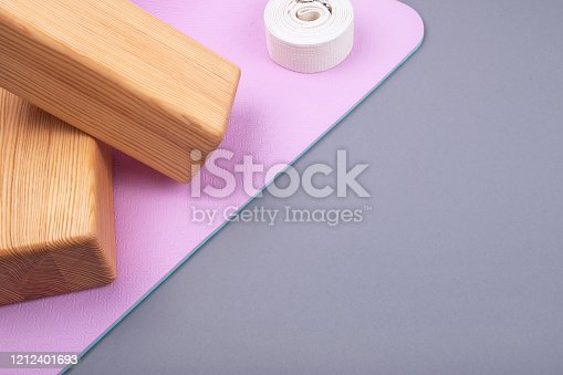 637596492 istock photo Top view of blue pink mat, two wooden blocks and twisted white belt on grey background.  Space for  text. 1212401693