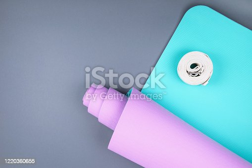 637596492 istock photo Top view of blue pink yoga mat and twisted white belt on grey background.  Space for  text. 1220360655