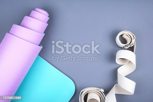 637596492 istock photo Top view of blue pink yoga mat and twisted white belt on grey background.  Space for  text. 1225602688
