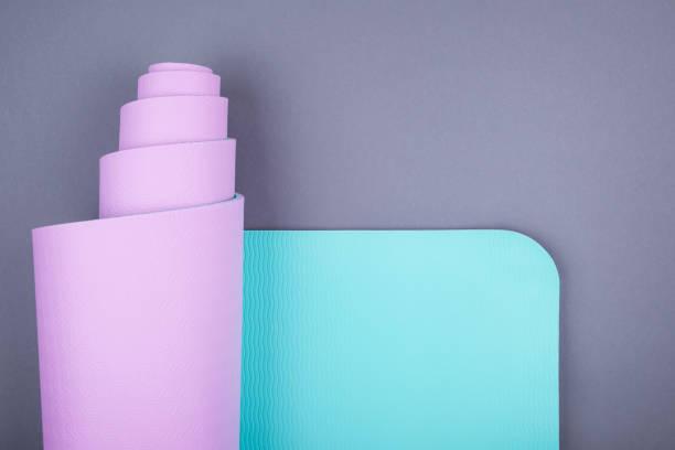 Top-Ansicht der blau rosa Yogamatte auf grauem Hintergrund.  Platz für Text. – Foto
