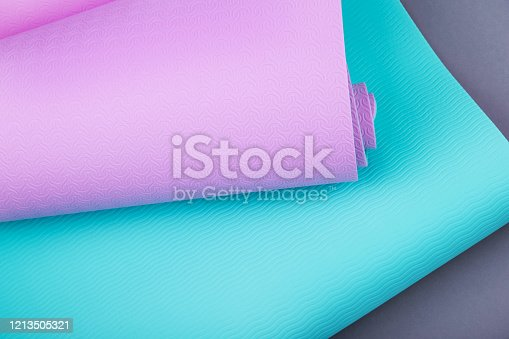 637596492 istock photo Top view of blue pink yoga mat on grey background.  Space for  text. 1213505321