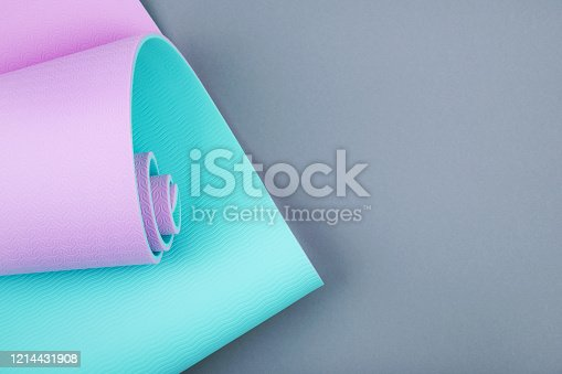 637596492 istock photo Top view of blue pink yoga mat on grey background.  Space for  text. 1214431908