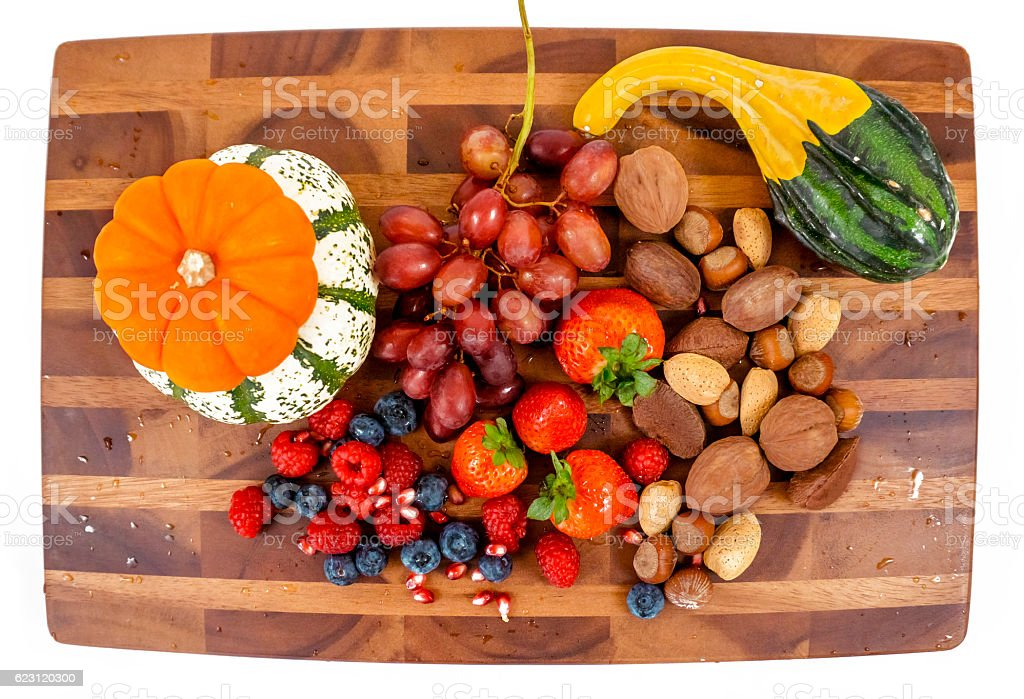 Top view of board with fruit, pumpkins and nuts stock photo