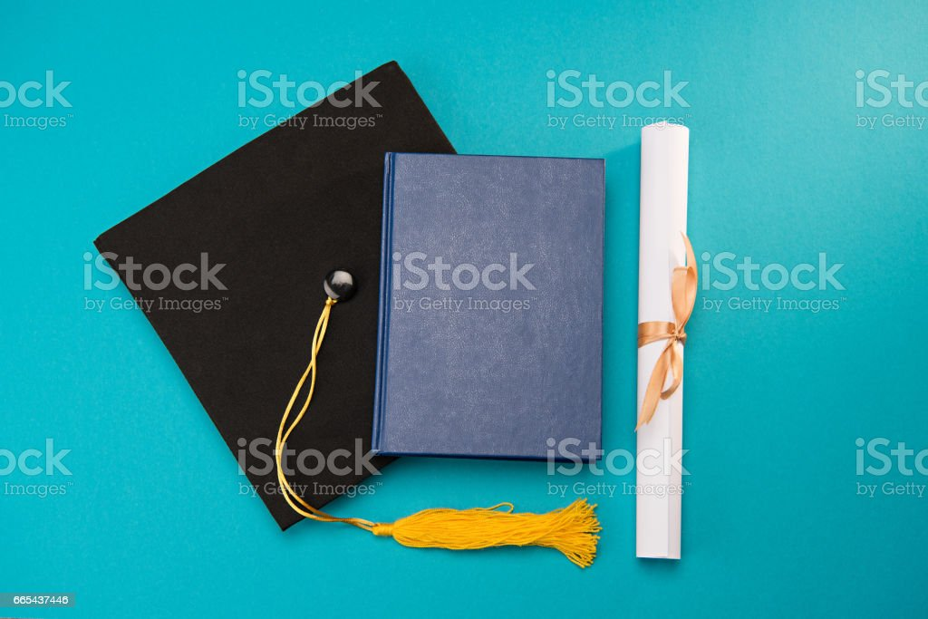 Top view of book, graduation mortarboard and diploma on blue, education concept stock photo