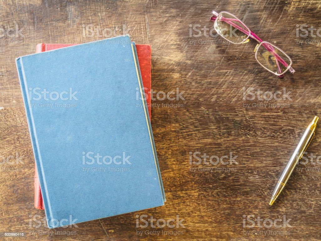 top view of book, pen and glasses on wooden background - Photo