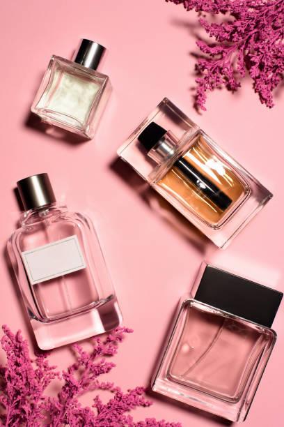 widok z góry butelek perfum z różowymi kwiatami - perfumowany zdjęcia i obrazy z banku zdjęć