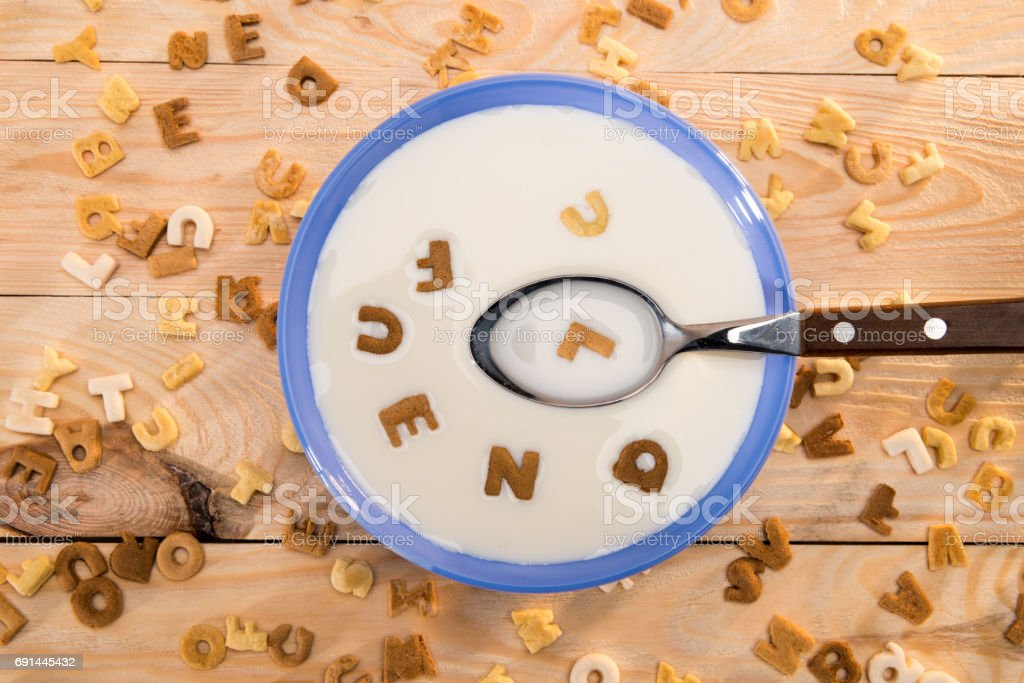 Top view of bowl with milk and spoon and alphabet corn flakes on wooden table stock photo