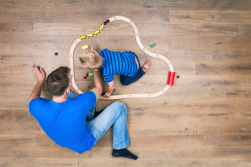 Top view of boy and father playing with his train