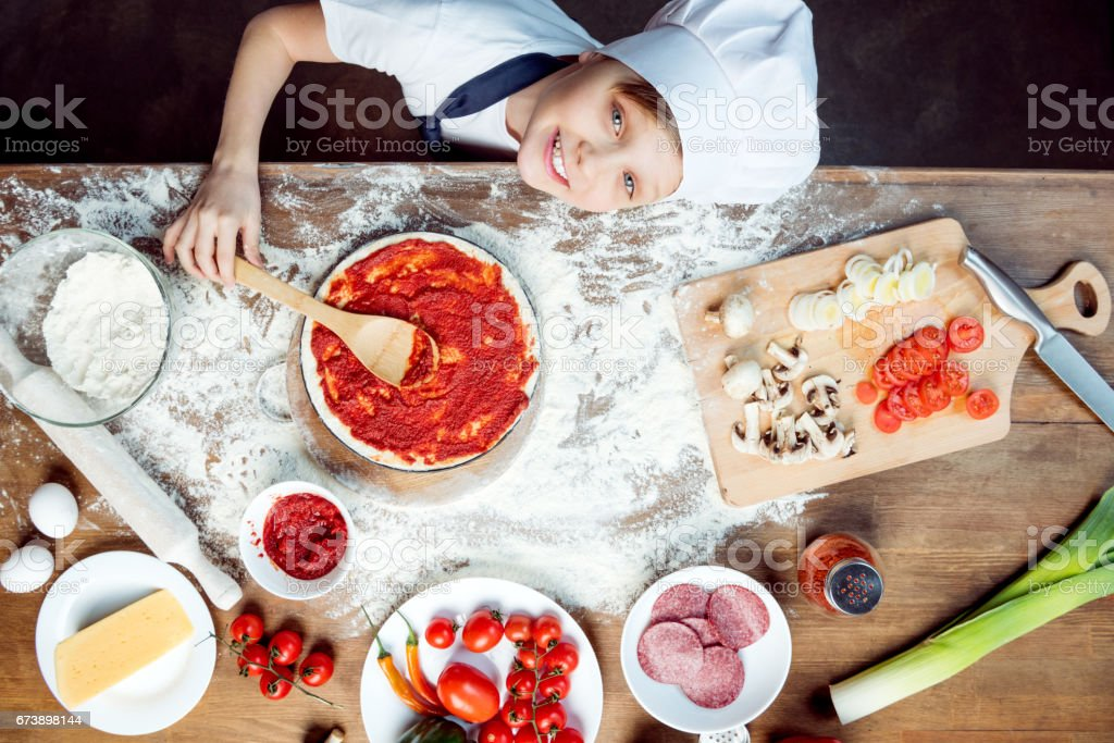 top view of boy making pizza with pizza ingredients, tomatoes, salami and mushrooms on wooden tabletop stock photo