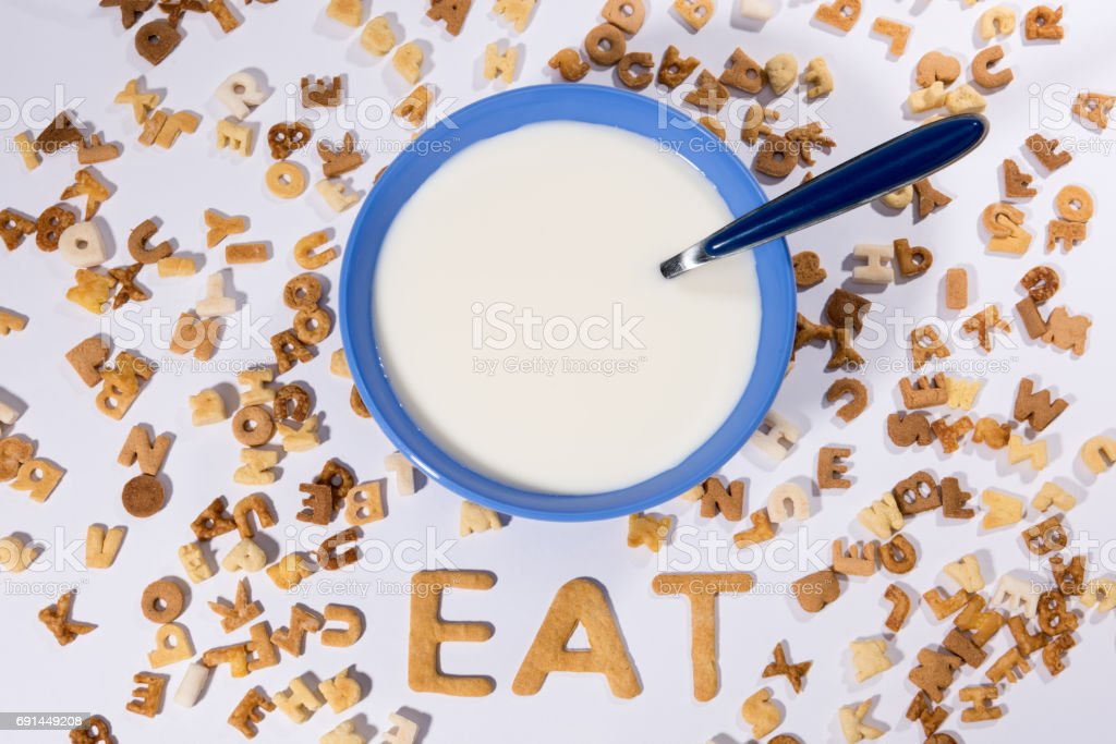 Top view of breakfast cereal alphabet, milk in bowl and word eat isolated on grey stock photo