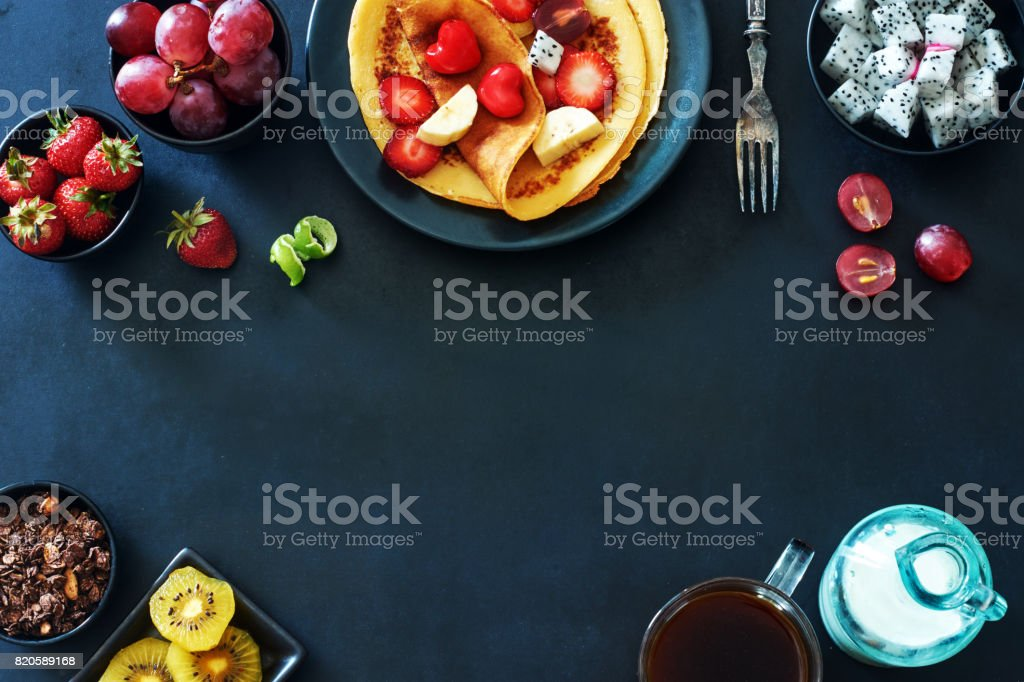 Top view of breakfast with crepes with strawberries, grapes, kiwi, chocolate granola, coffee and milk over dark background. stock photo