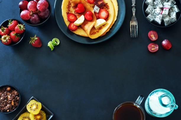draufsicht auf das frühstück mit crepes mit erdbeeren, trauben, kiwi, schokolade, müsli, kaffee und milch auf dunklem hintergrund. - gebackene banane stock-fotos und bilder