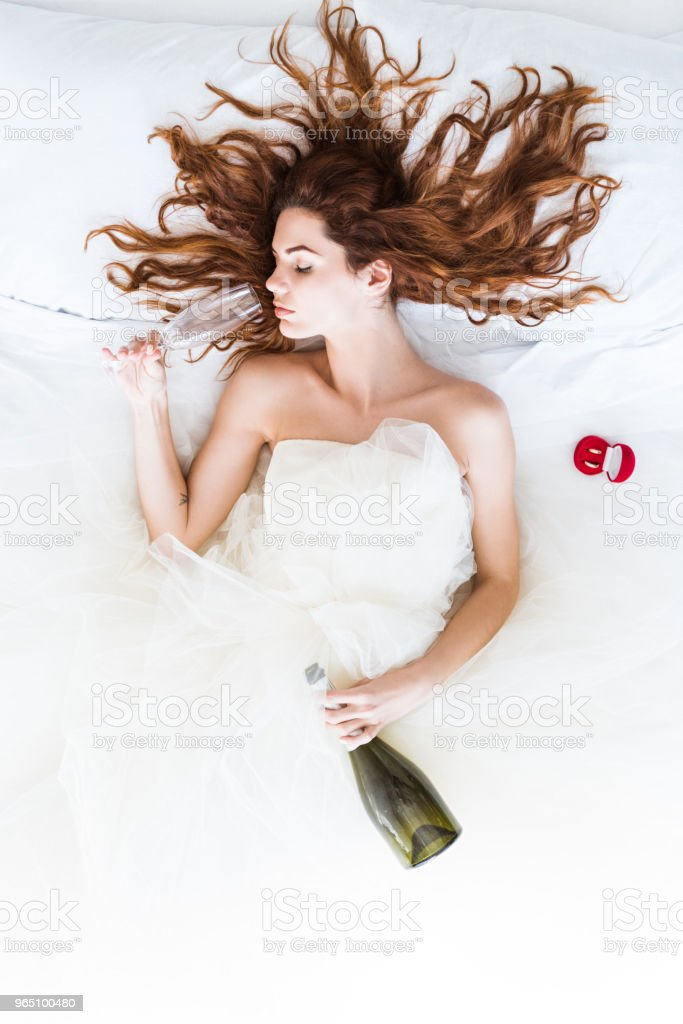 Top view of bride wearing white dress lying in bed and drinking champagne zbiór zdjęć royalty-free