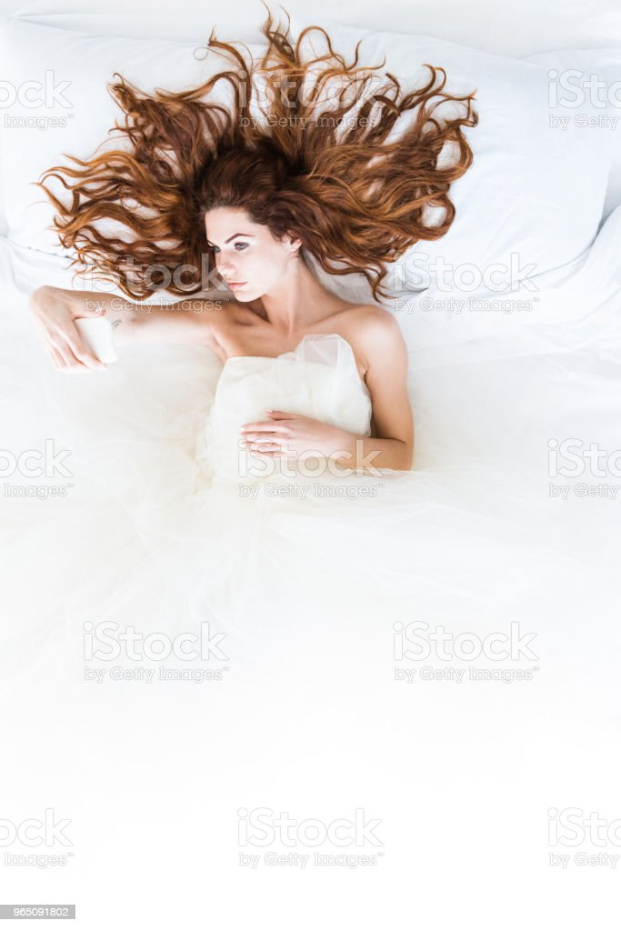Top view of bride wearing white dress lying in bed and taking selfie royalty-free stock photo