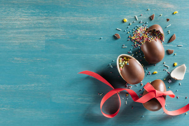 top view of broken chocolate easter eggs on turquoise surface stock photo
