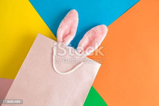 istock Top view of bunny ears in shopping bag on multicolored background abstract. 1136804881