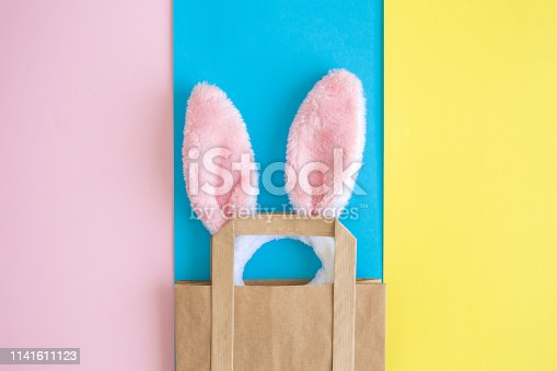 1136804881 istock photo Top view of bunny ears in shopping bag on multicolored background abstract. 1141611123