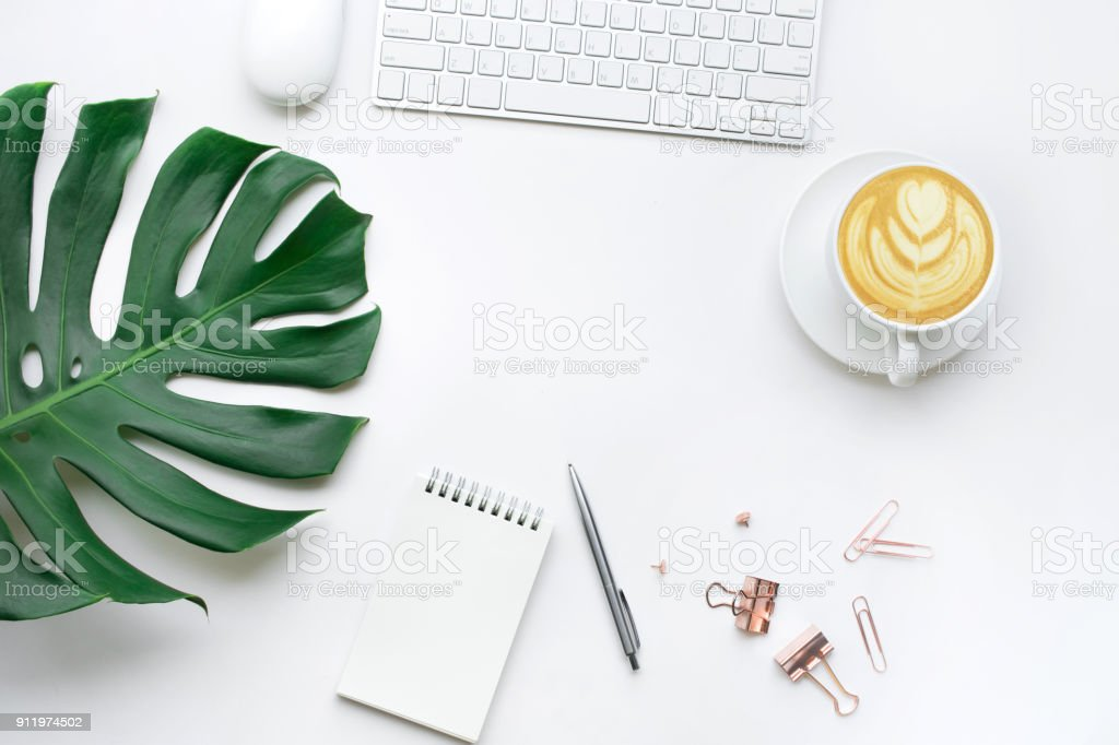 Top view of business desk table with monstera leaves and mock up accessories on white background.flat lay design.