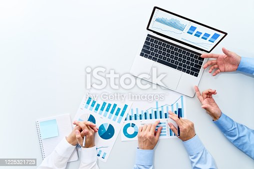 Reports and laptops on white table.