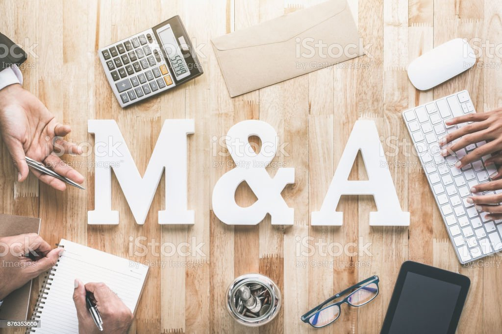 Top view of business office workstation with M&A letters or merger and acquisition stock photo