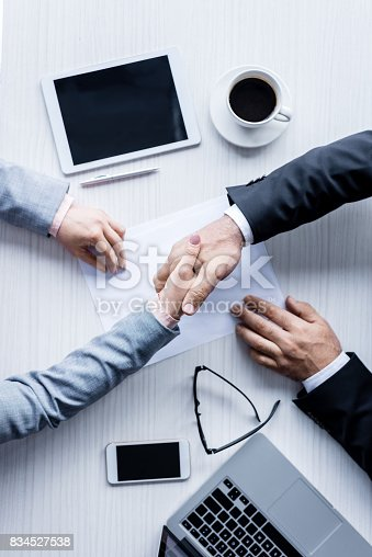 istock top view of business people shaking hands during meeting 834527538