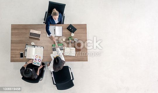 Top view of business people shaking hands after sealing a deal. High angle view of casual businesswomen handshake after concluding business agreement.