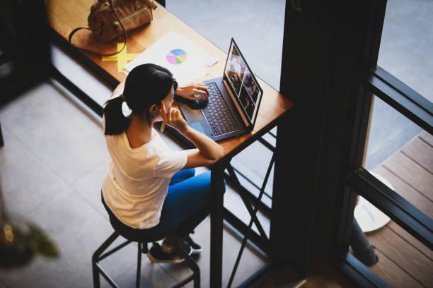 vista superior de la mujer de negocios hablando con sus colegas sobre el plan en la videoconferencia - foto de stock