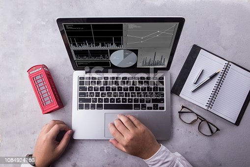 istock Top view of businessman using laptop computer with statistics data on a screen. Working with financial graphs charts, using business software for data analysis and project management concept. 1084924186