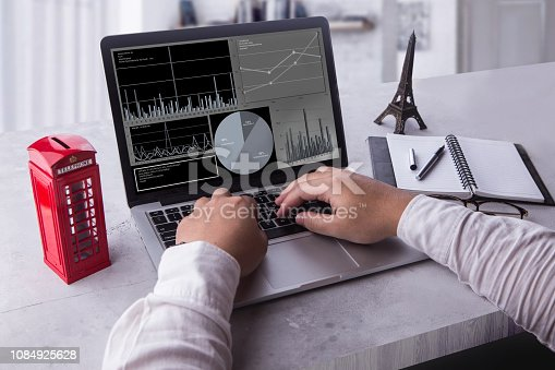 istock Top view of businessman using laptop computer with statistics data on a screen. Working with financial graphs charts, using business software for data analysis and project management concept. 1084925628