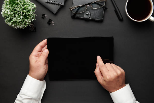 Top-Ansicht der Hände des Geschäftsmannes arbeiten mit Tablet-PC. Moderner schwarzer Bürotisch mit Notizbuch, Stift und vielen Dingen. Flaches Laientabellenlayout. Kopieren Sie Speicherplatz für Text. – Foto