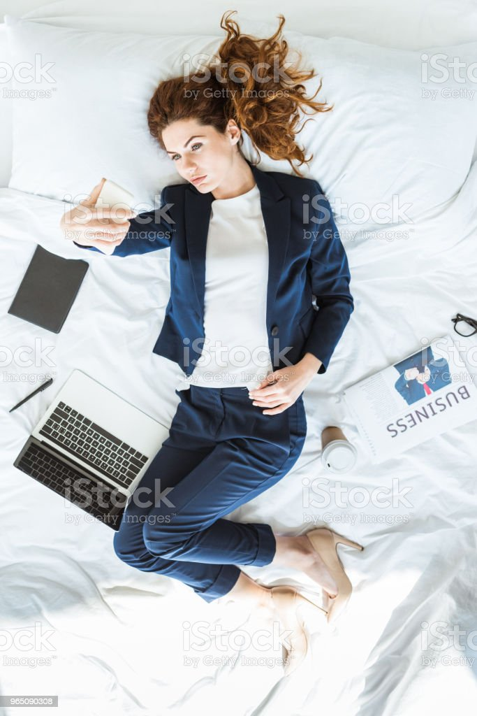 Top view of businesswoman in suit taking selfie in bed among folders and documents zbiór zdjęć royalty-free