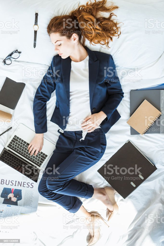 Top view of businesswoman in suit typing on laptop while lying in bed among folders and documents royalty-free stock photo