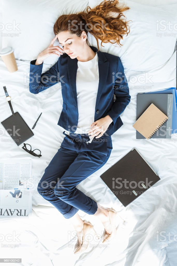 Top view of businesswoman wearing suit sleeping in bed among folders and documents zbiór zdjęć royalty-free