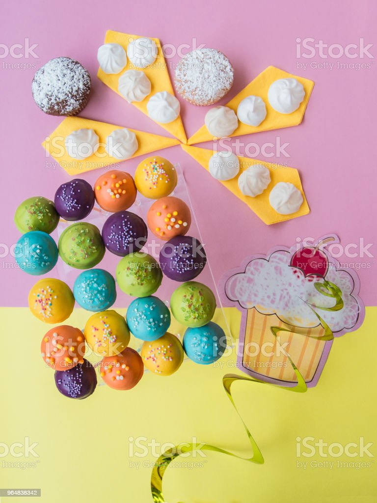 Top view of cake pops on a colorful pink-yellow background royalty-free stock photo